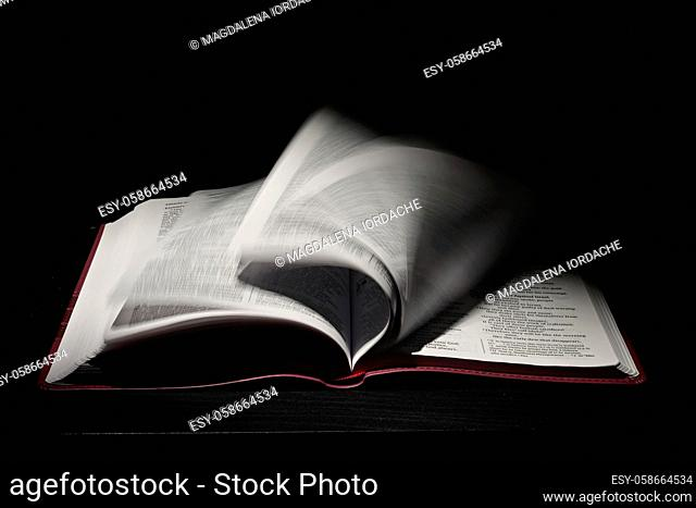 An Open Holy Bible Moving Pages on Dark Bckground