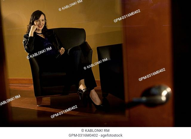Portrait of businesswoman relaxing in leather armchair