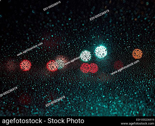 raindrops on the glass on blur background of colored spots