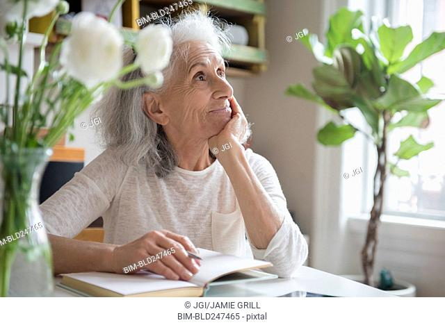 Pensive older woman writing in journal