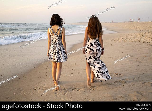 Two pretty girls walking on the seashore at sunset one summer afternoon
