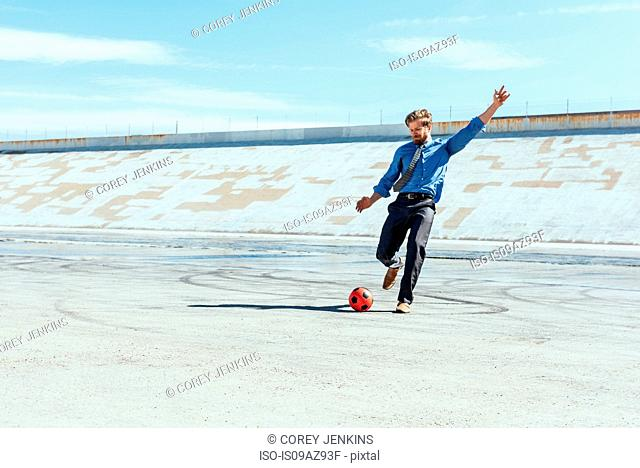 Businessman playing soccer on Los Angeles river, California, USA