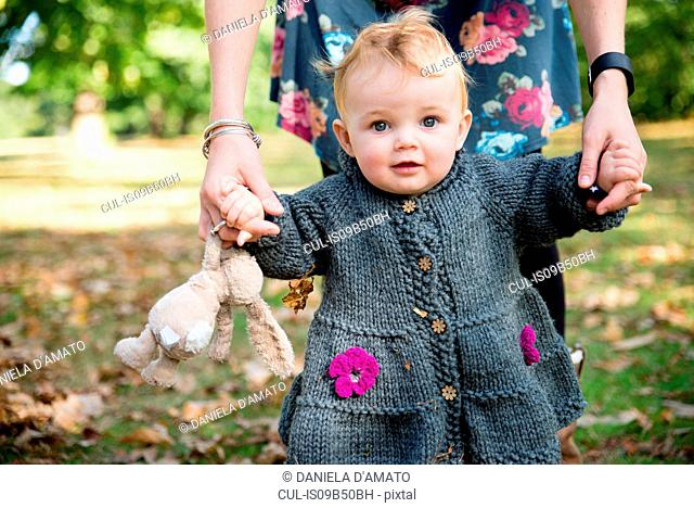 Portrait of baby girl holding mother's hands and toddling in park