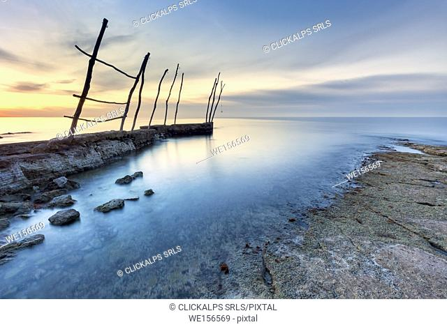 Europe, Croatia, Istria, Adriatic coast, Umag, village Savudrija. The bay at sunset with traditional wooden poles for fishing boats