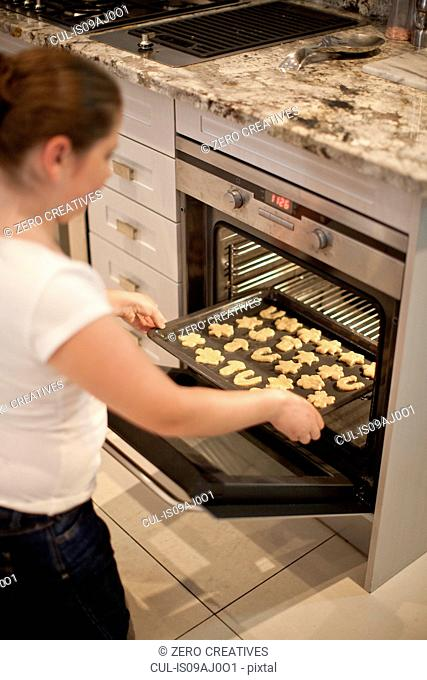 Teenage girl placing baking tray of biscuits in oven