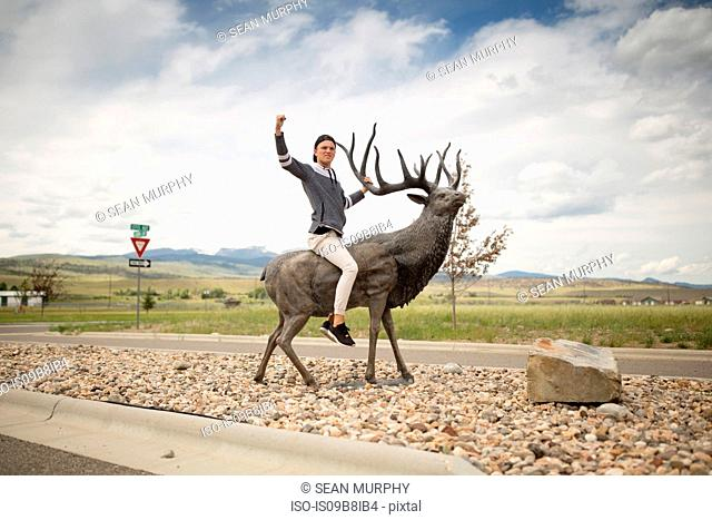 Teenage boy sitting on statue of stag