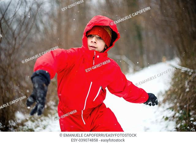 portrait of teenager with red jacket and hat in the snowy forest, throws a snowball