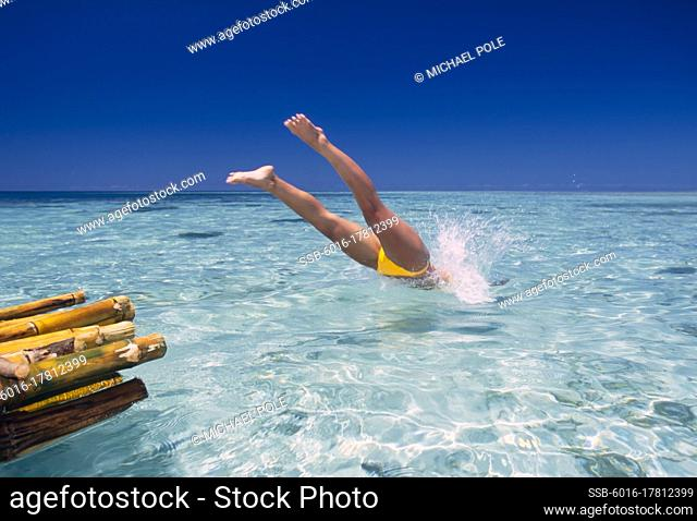 Woman diving into tropical water from bamboo raft