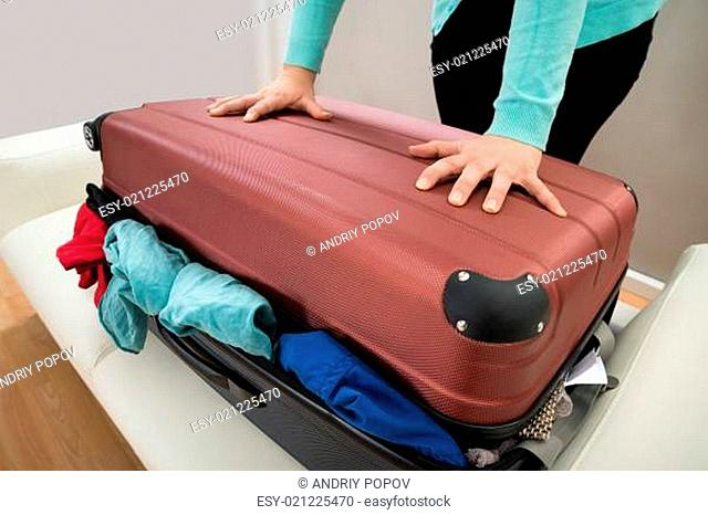 Close-up Of Woman Trying To Close Suitcase With Excess Of Clothes