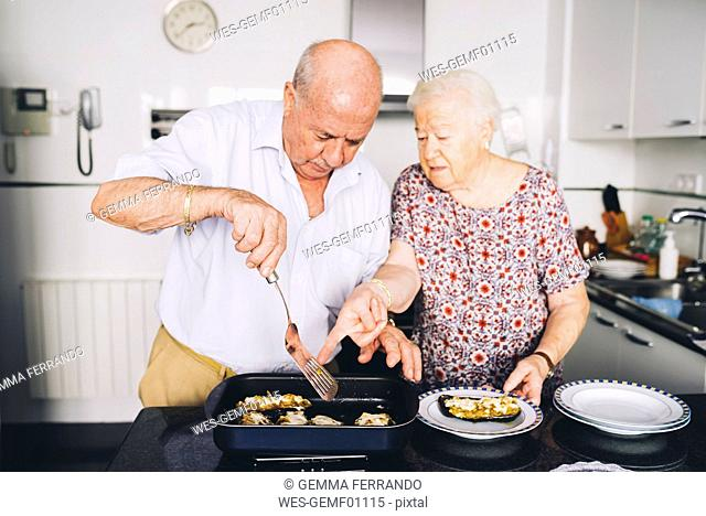 Senior couple serving stuffed eggplants in the kitchen