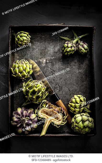 Whole and halved artichokes on black metal tray