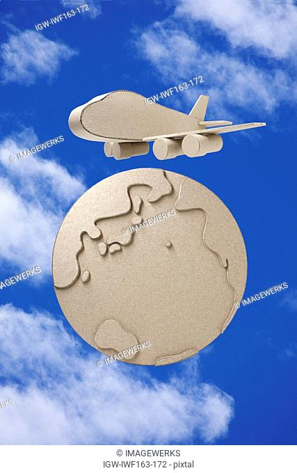 Paper globe and airplane against sky digital composite