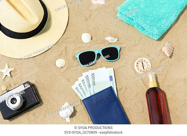 money in passport, shades and hat on beach sand