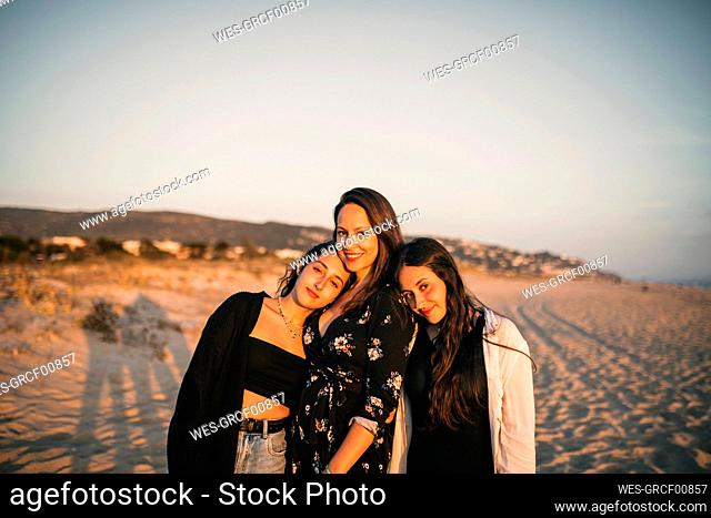 Smiling daughters leaning on shoulder of mother at beach