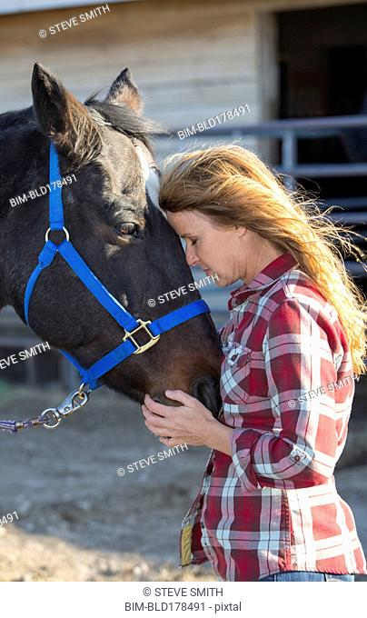Caucasian woman hugging horse on ranch