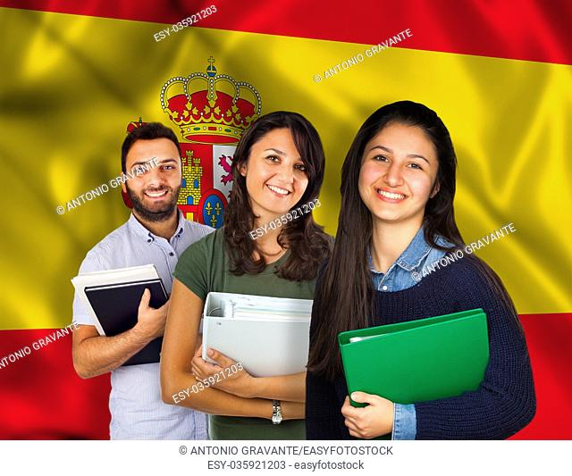 Couple of young students with books over spanish flag
