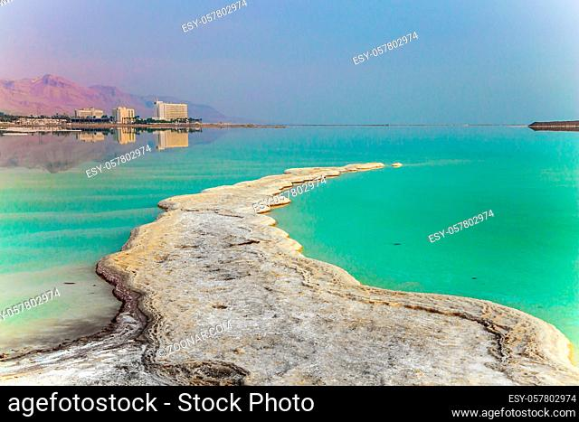 Early morning at the resorts of the Dead Sea. Israel. Azure sea water is full of healing salts. Small islets of evaporated salt in the water