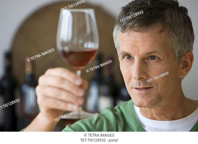 Man looking at glass of wine