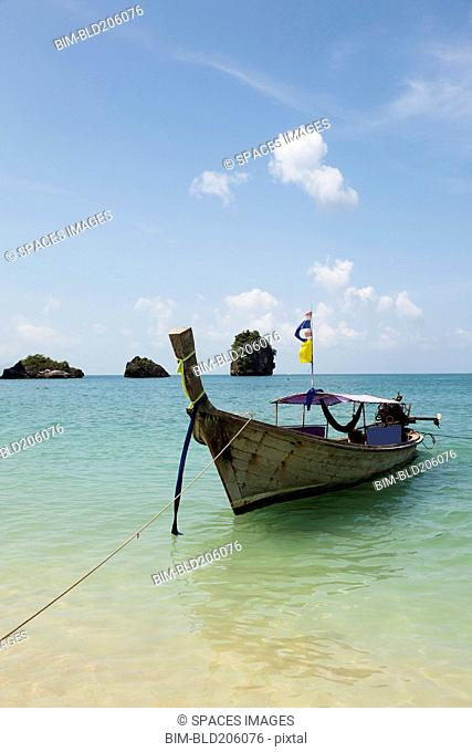 A traditional long tail boat moored in shallow water on Tham Phra Nang beach