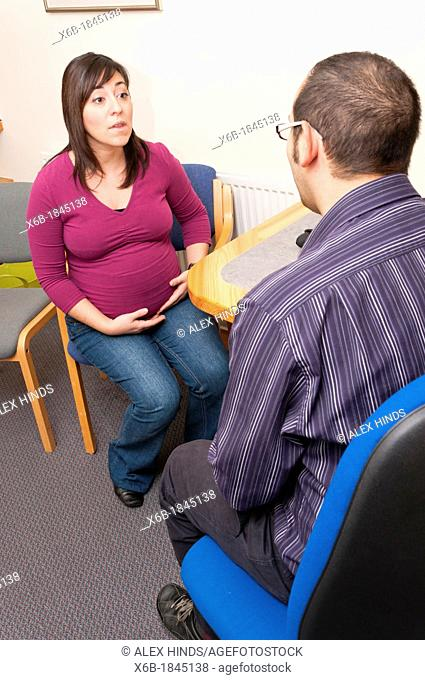 GP Doctor surgery patient consultation with pregnant woman