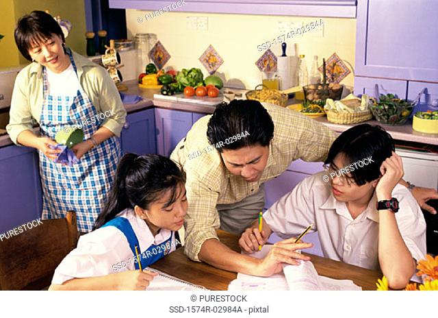 Father helping his son and daughter with their homework