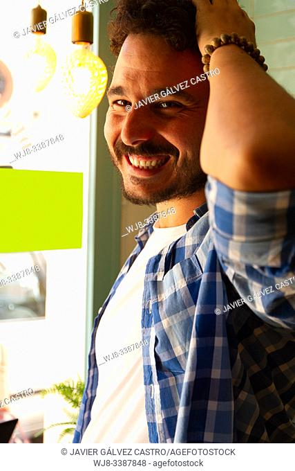young man posing with natural light from window with carefree pose smiling