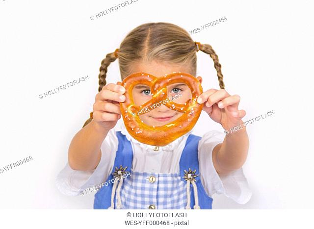 Portrait of smiling little girl looking through pretzel