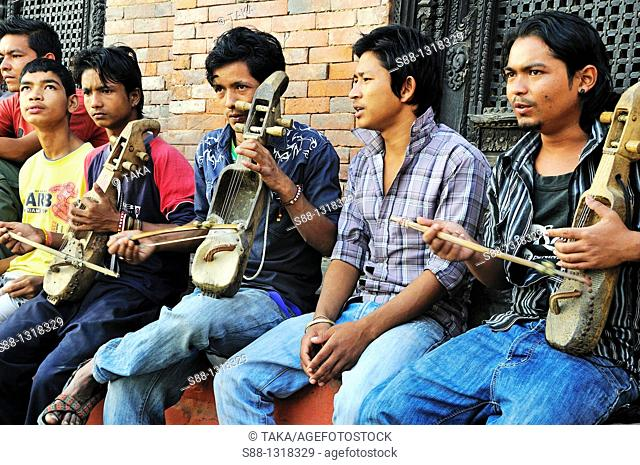 Grope of young Nepali men play and singing at at Durbar Square on the day of Indra Jatra festival, Kathmandu Nepal