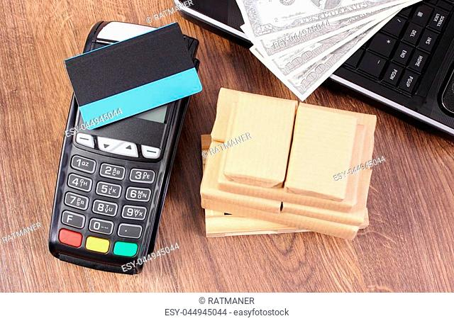 Payment terminal with contactless credit card, currencies dollar, laptop and small wrapped boxes on wooden pallet, concept of paying for products and shipping