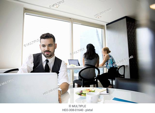 Businessman using laptop eating lunch in office cafeteria