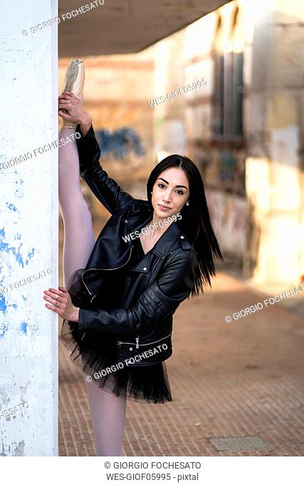 Italy, Verona, portrait of young woman wearing leather jacket and tutu stretching