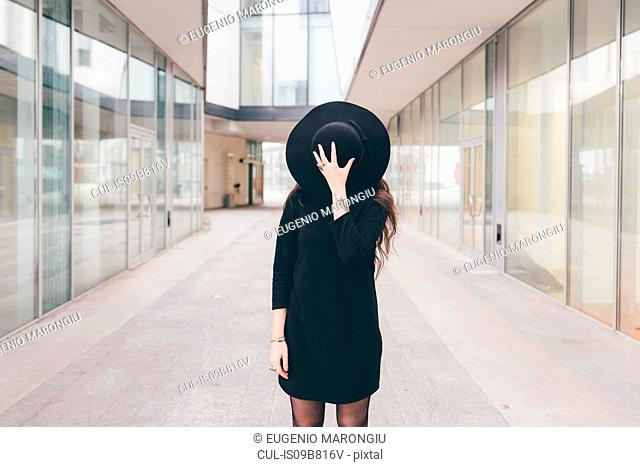 Portrait of young woman in urban environment, covering face with hat