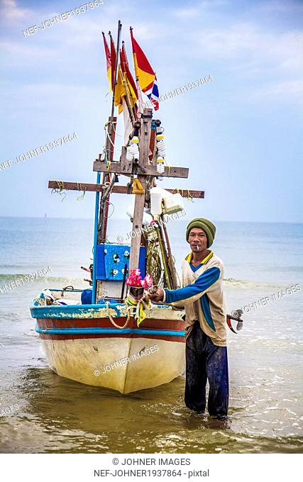 Fisherman with fishing boat, Thailand