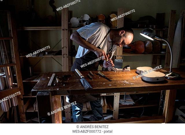 Luthier using a chisel on a violin scroll during the manufacture of a violin in his workshop