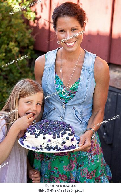 Portrait of mother and daughter, woman holding cake