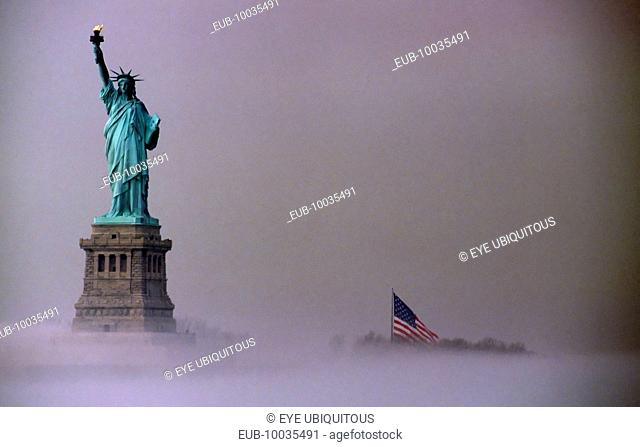 Statue of Liberty and Stars and Stripes Flag on misty morning