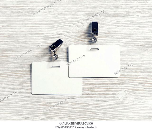Two blank plastic badges mockup on light wood table background. Empty ID mock up. Copy space for text. Flat lay
