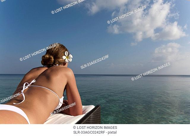 Woman laying on daybed overlooking sea