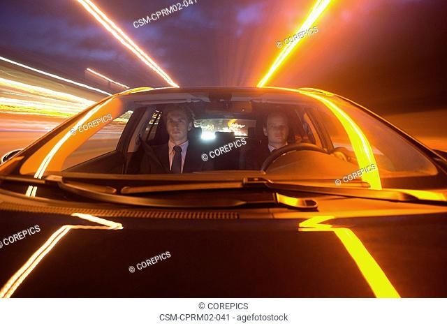 Two businessmen driving in a car over a motorway at night