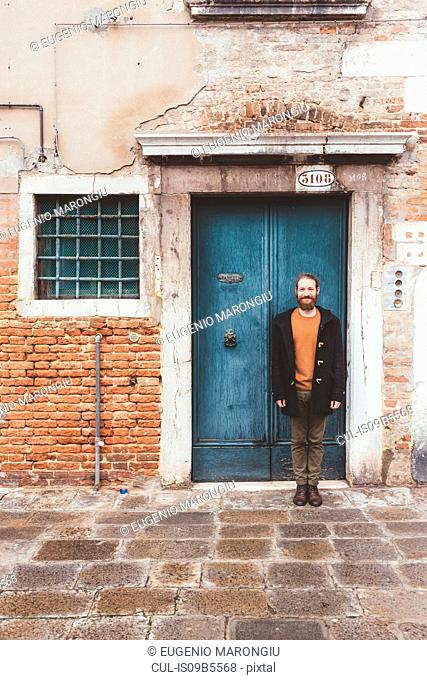 Portrait of bearded mid adult man standing in front of old doorway, Venice, Italy