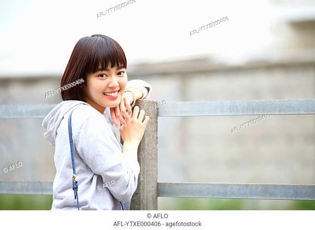 Young Japanese woman by a railway track outside