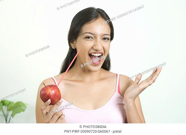 Woman drinking juice from an apple with a straw