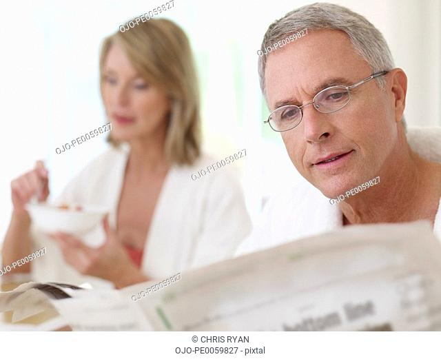Couple indoors reading newspaper and eating breakfast