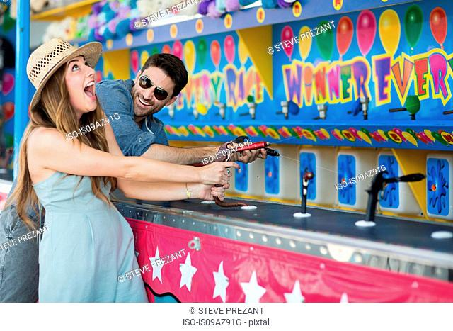 Couple at fairground shooting gallery, Coney island, Brooklyn, New York, USA