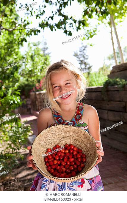 Caucasian girl holding basket of cherries