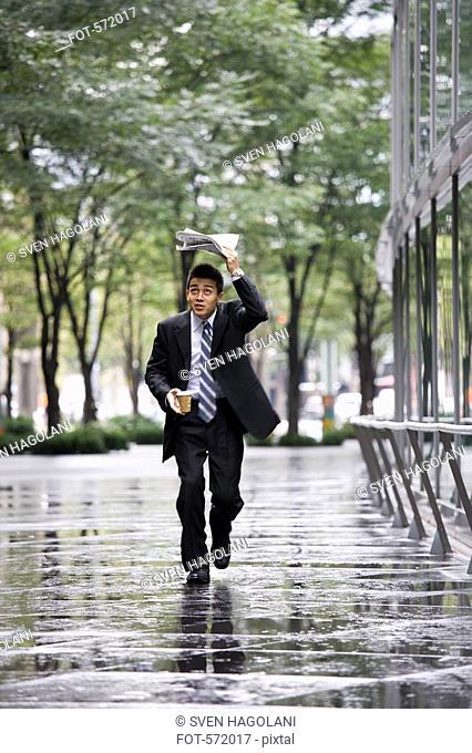 A businessman running in the rain