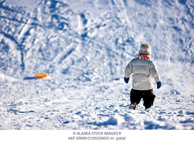 Toddler walking down a sled hill to retreive her sled, Winter, Anchorage, Southcentral Alaska