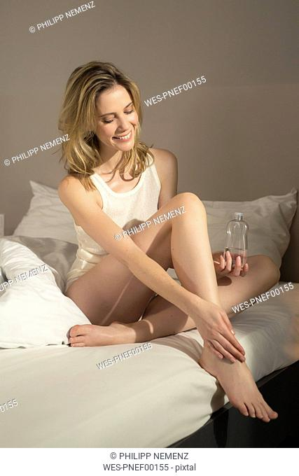 Smiling woman in bed applying skin oil