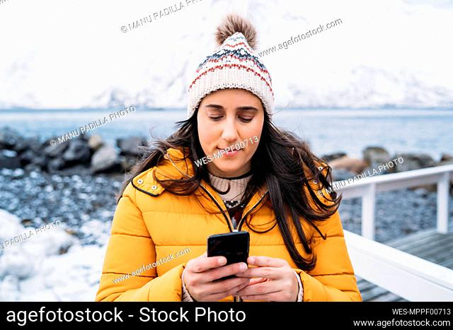 Tourist using cell phone at the coast, Lofoten, Norway