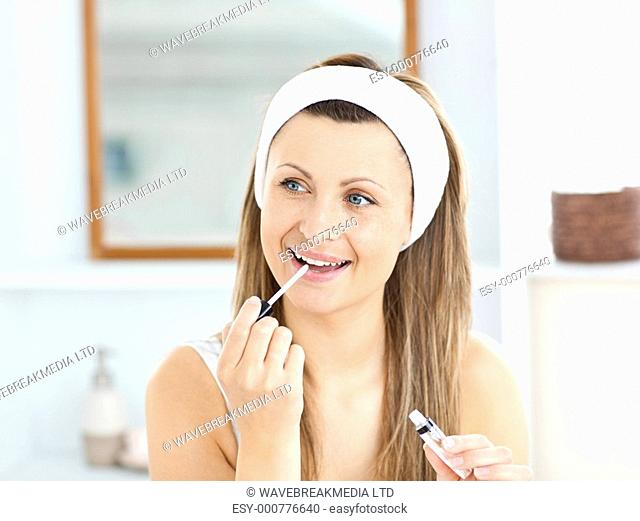 Happy woman applying gloss on her lips in the bathroom at home